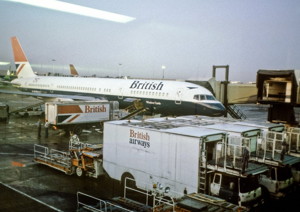 Free image of British Airways plane sitting on the runway at the gate, with workers down below loading luggage.