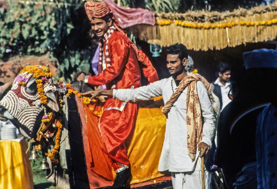 Free image of Honored person being helped by his attendant on horseback, in bright ceremonial clothes, Asia