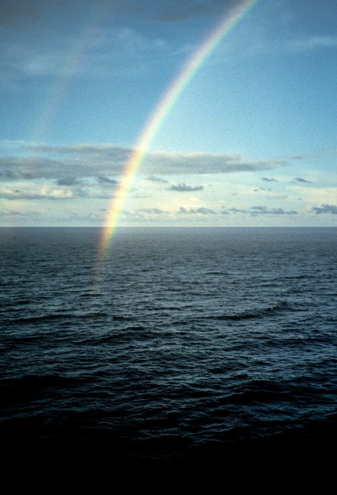Free image of Rainbow above blue water.