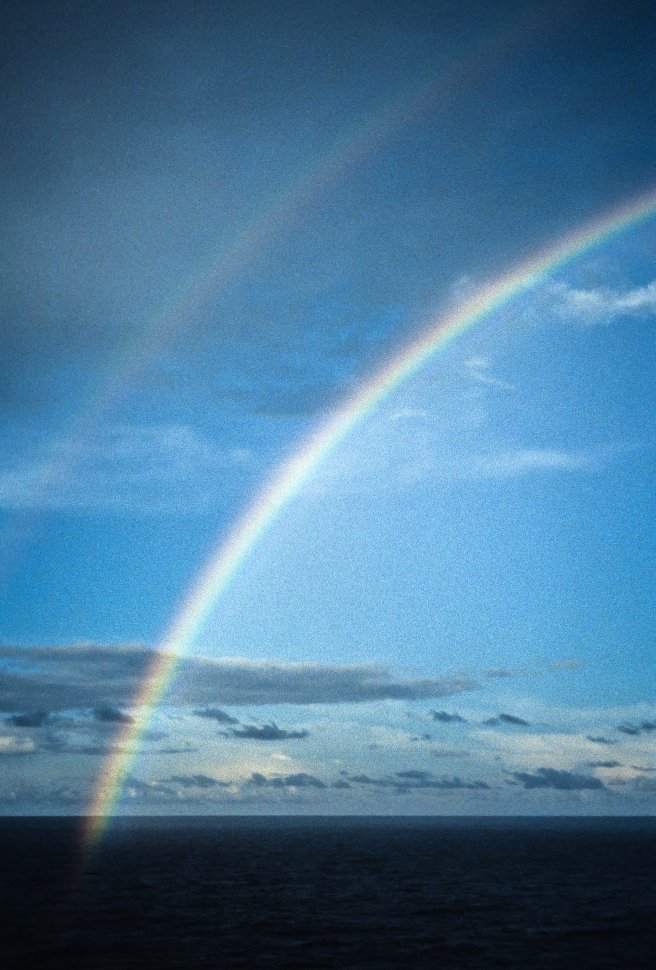 Free image of Rainbow above blue ocean.