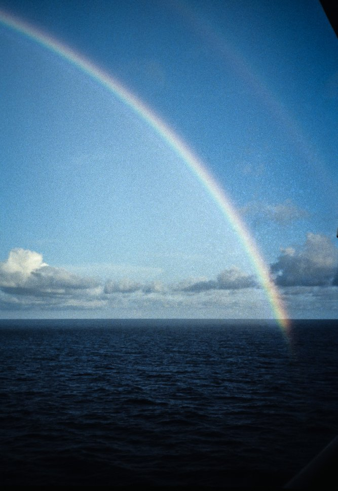 Free image of Rainbow on blue water.