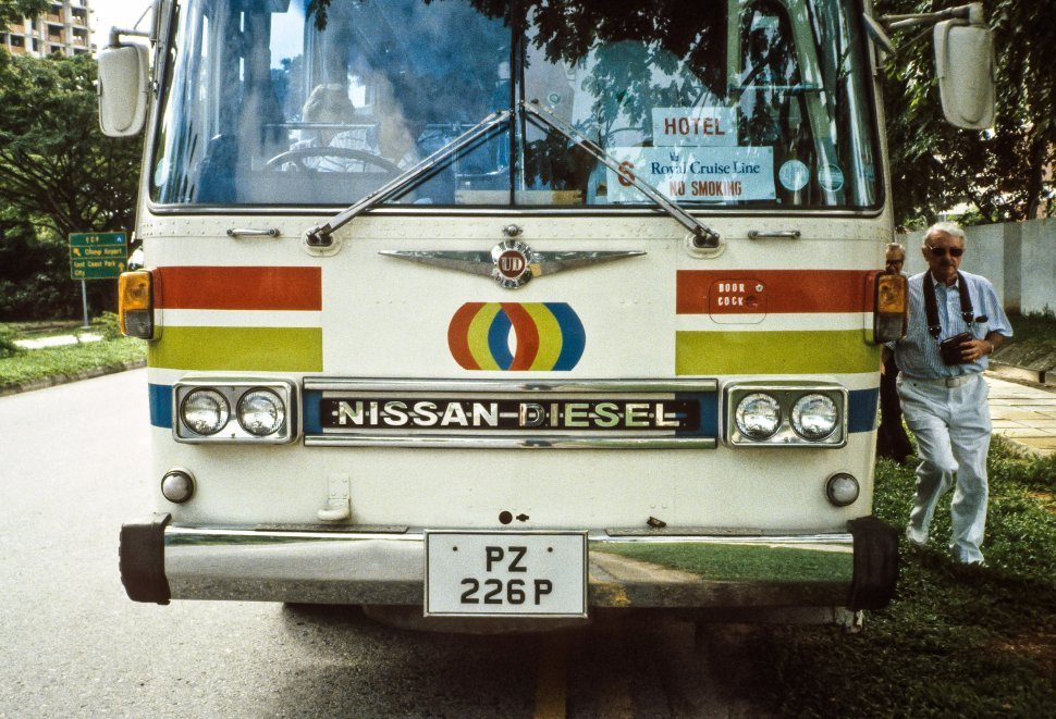 Free image of Close up of the front end of a tour bus and man walking with his camera, Europe