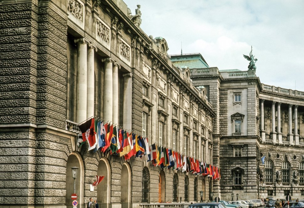 Free image of Flags hanging from a large columned building, Europe