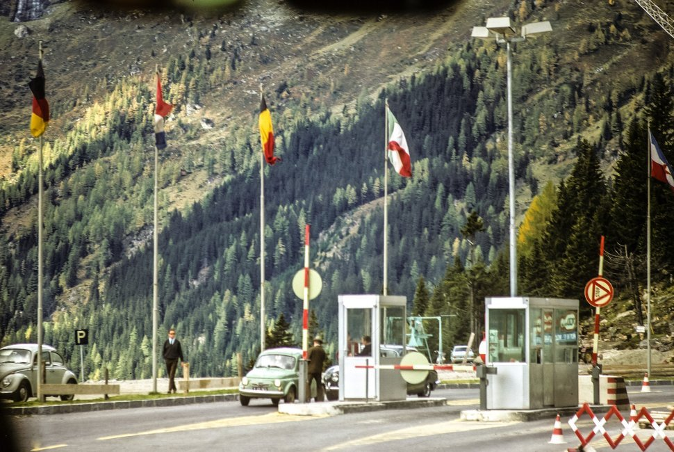 Free image of Guards at a mountain pass checkpoint with flags in the wind above.