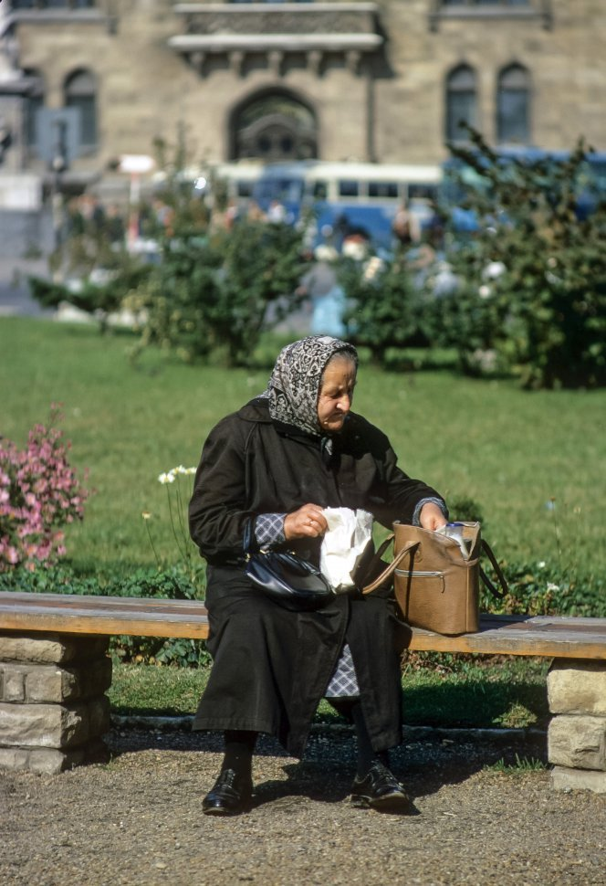 Free image of Elderly woman sitting on a bench eating her lunch.