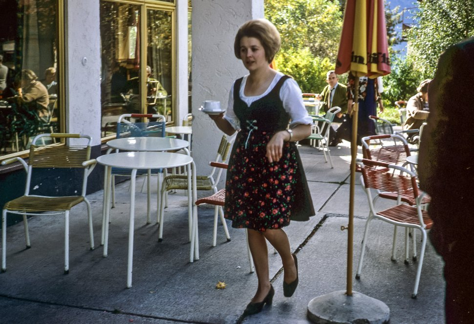 Free image of Woman walking with a coffee cup though a restaurant.