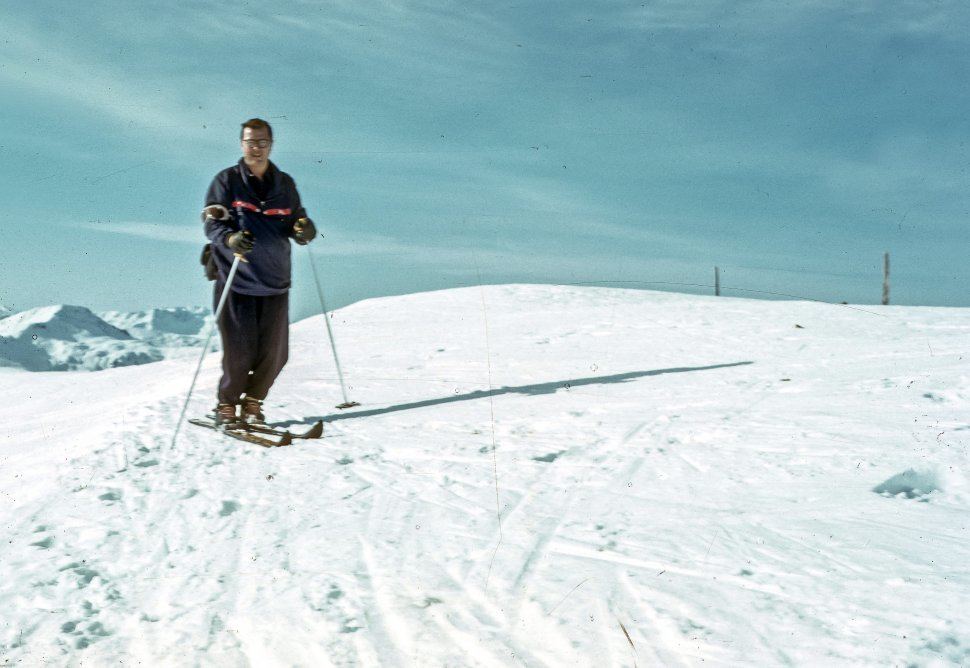 Free image of Man posing for a picture at the top of a ski area.