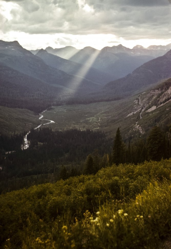 Free image of Sunbeams coming through the clouds down to a river valley.