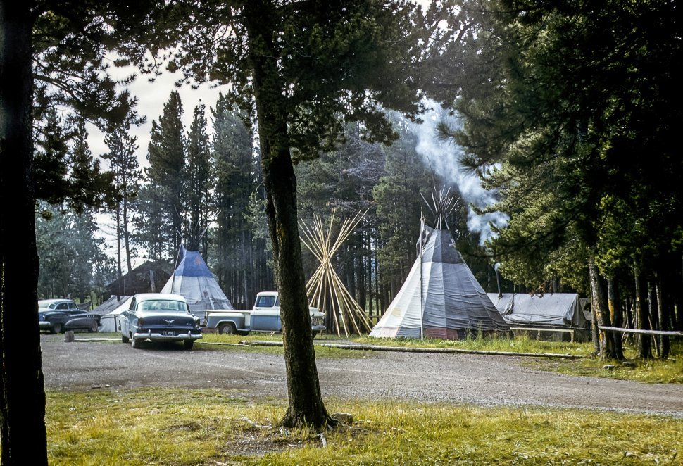 Free image of Campground with parked cars, teepees, and campfires, USA