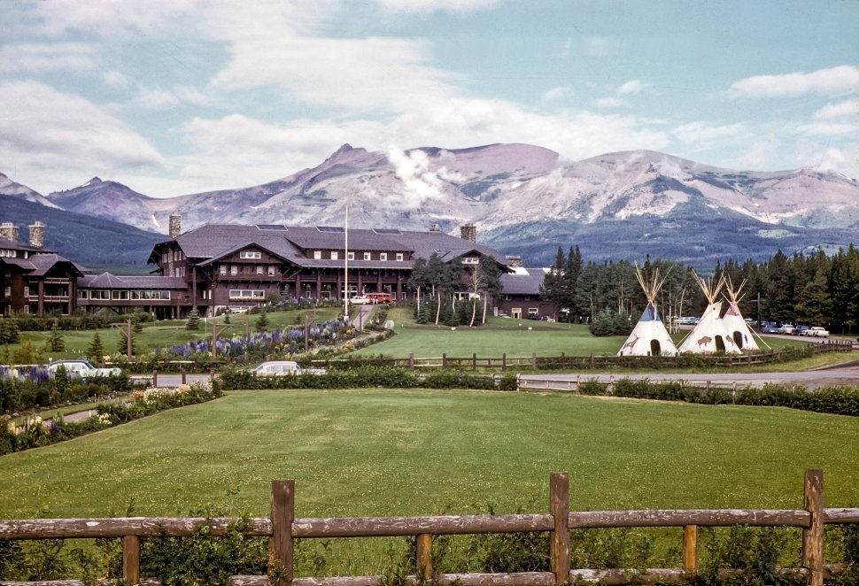 Free image of Mountain lodge hotel with mountains in the background and wigwams in the front.