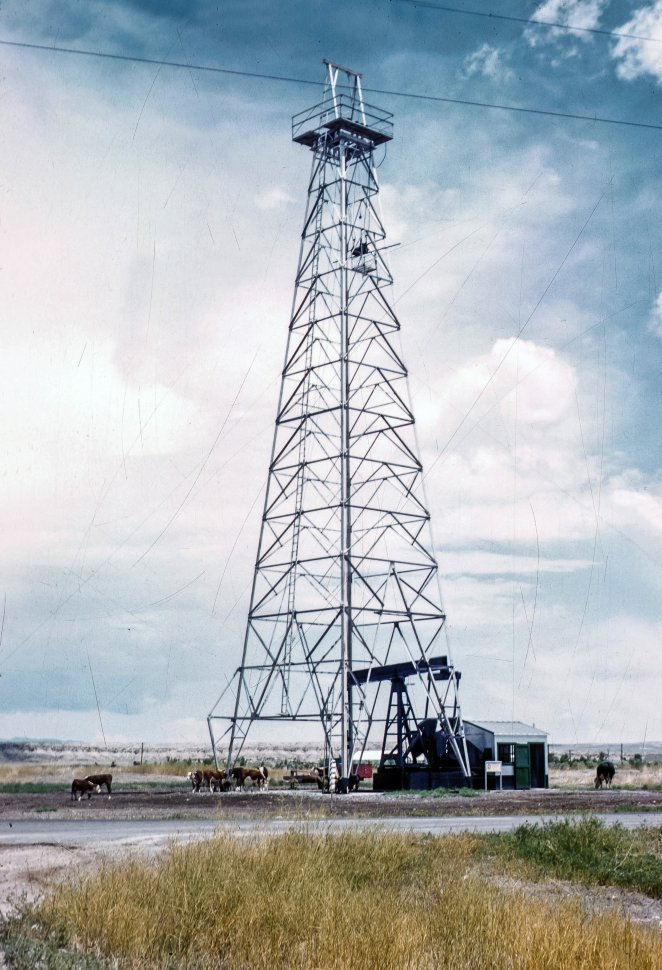 Free image of Oil well and scaffolding with horses below, in the desert.