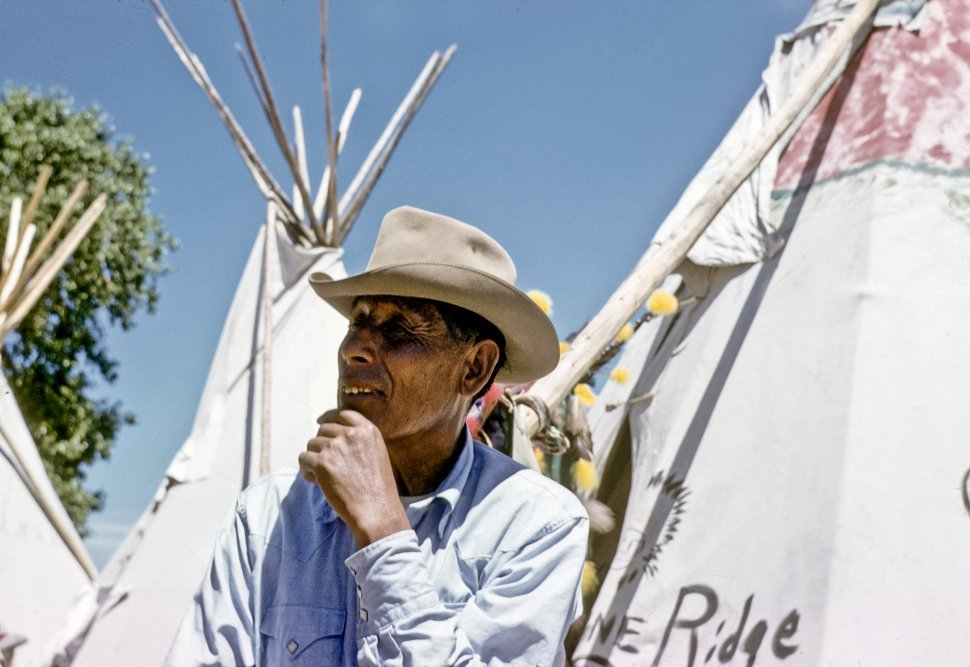 Free image of Man posing in front of a teepee smiling, USA