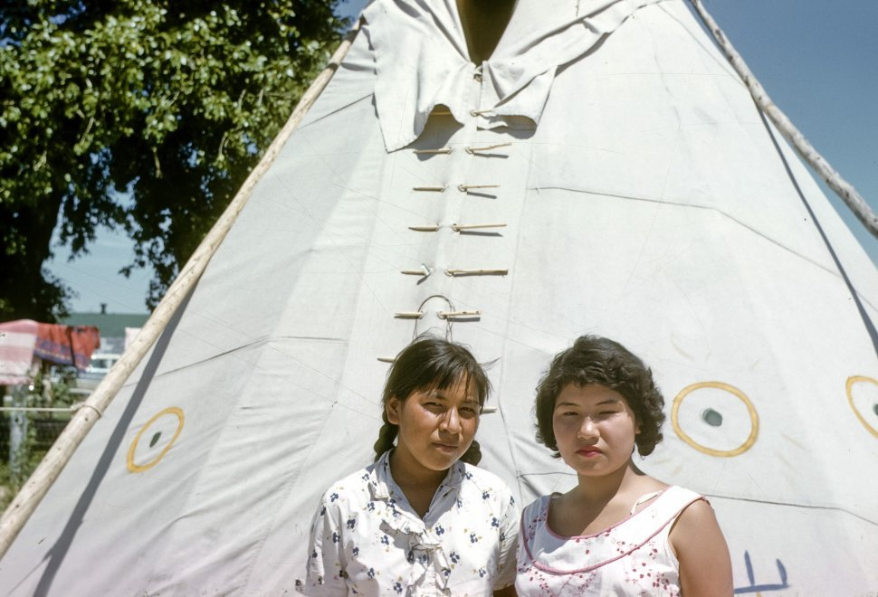 Free image of Two Native American women posing in front of a teepee, USA