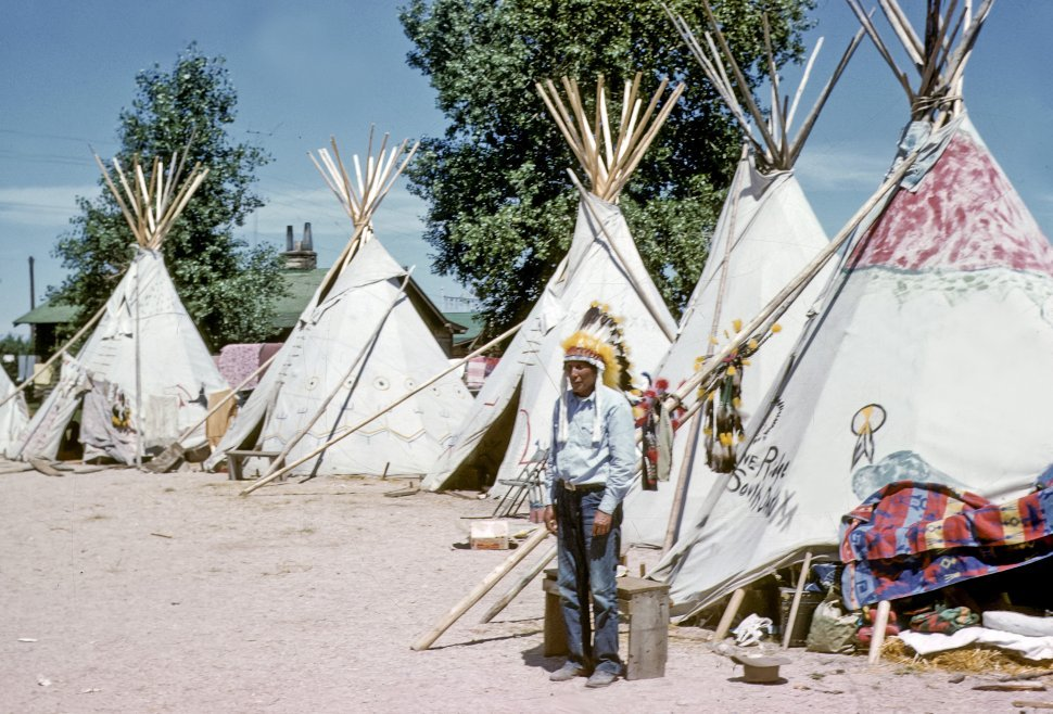 Free image of Native American in headdress posing in front of teepees, USA