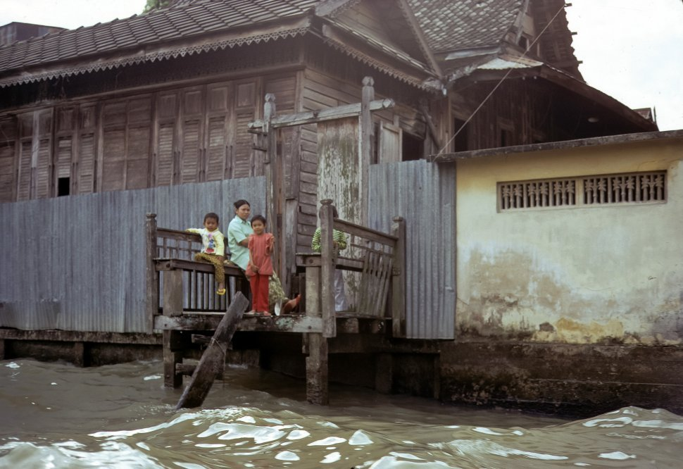 Free image of Mother and children standing on the front steps of their home on a canal, circa 1974, Hong Kong, China