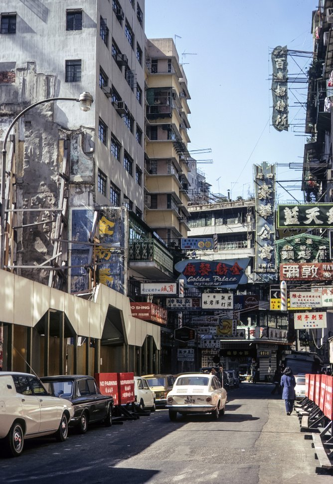 Free image of Stores, signs, and cars lining a street, circa 1974, Hong Kong, China