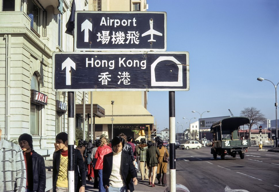 Free image of Crowd of people walking past traffic and signs in the street, circa 1974, Hong Kong, China