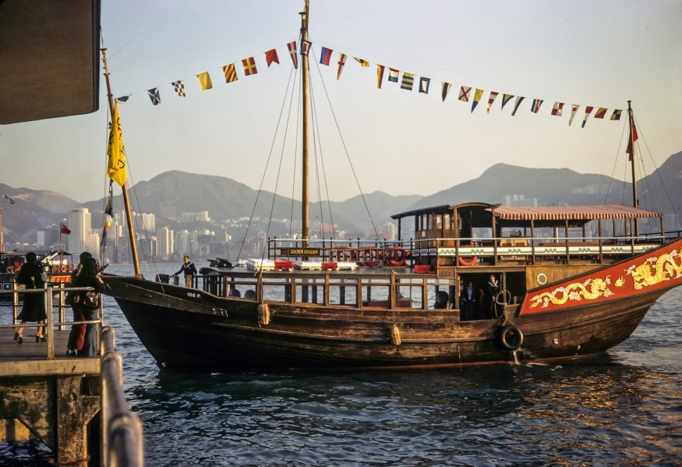 Free image of Antique fishing boat floating on the water with people waving from dock at sunset, circa 1974, Hong Kong, China