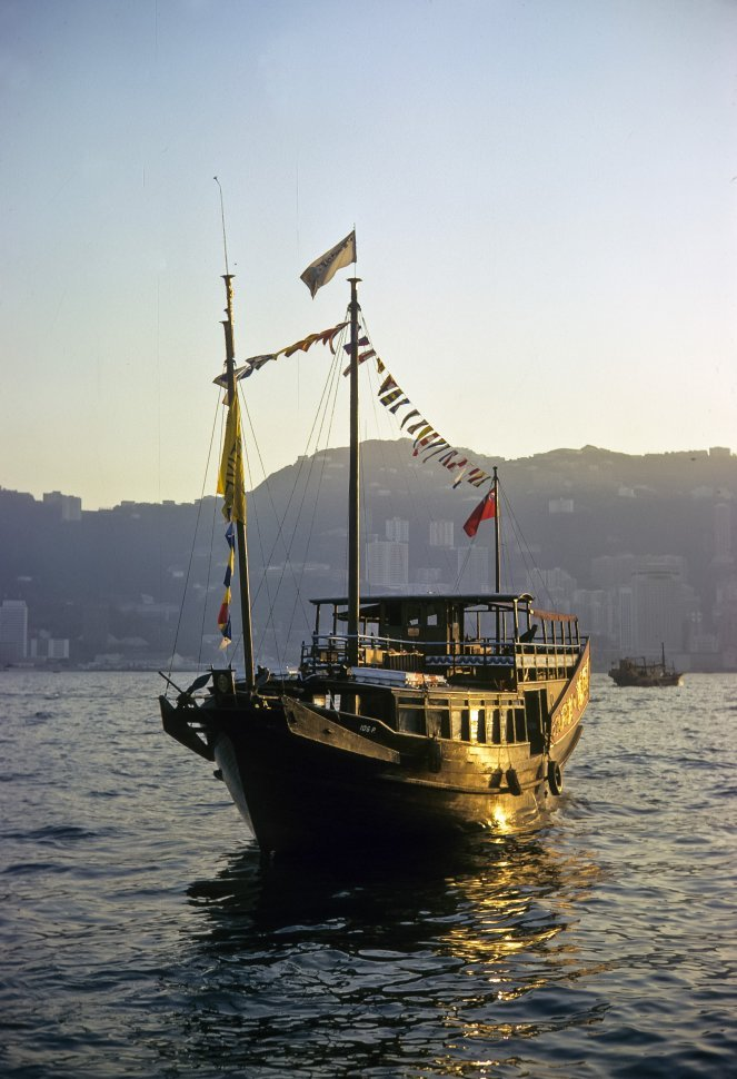 Free image of Antique fishing boat floating on the water in the sunset, circa 1974, Hong Kong, China
