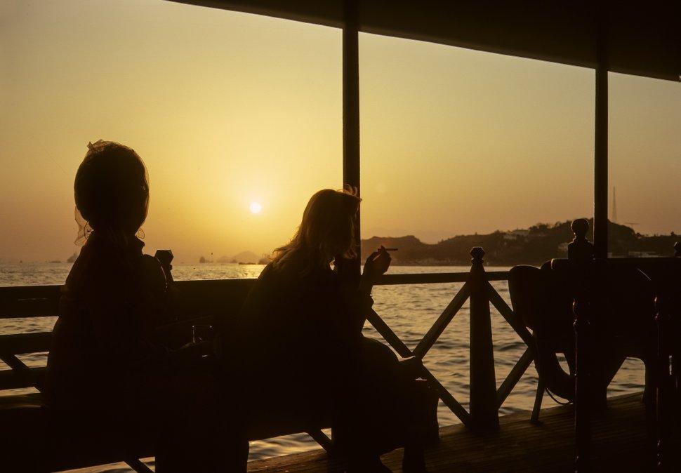 Free image of Silhouetted women sitting on a bench at sunset smoking, circa 1974, Hong Kong, China
