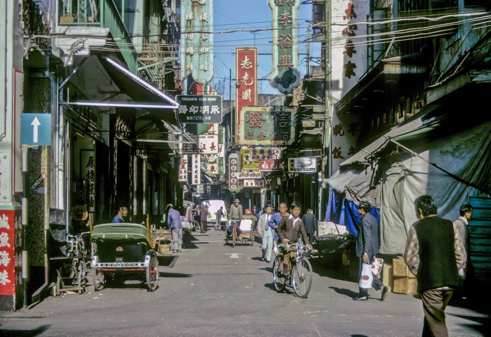 Free image of People walking down a city street crowded with signs and stores, circa 1974, Hong Kong, China