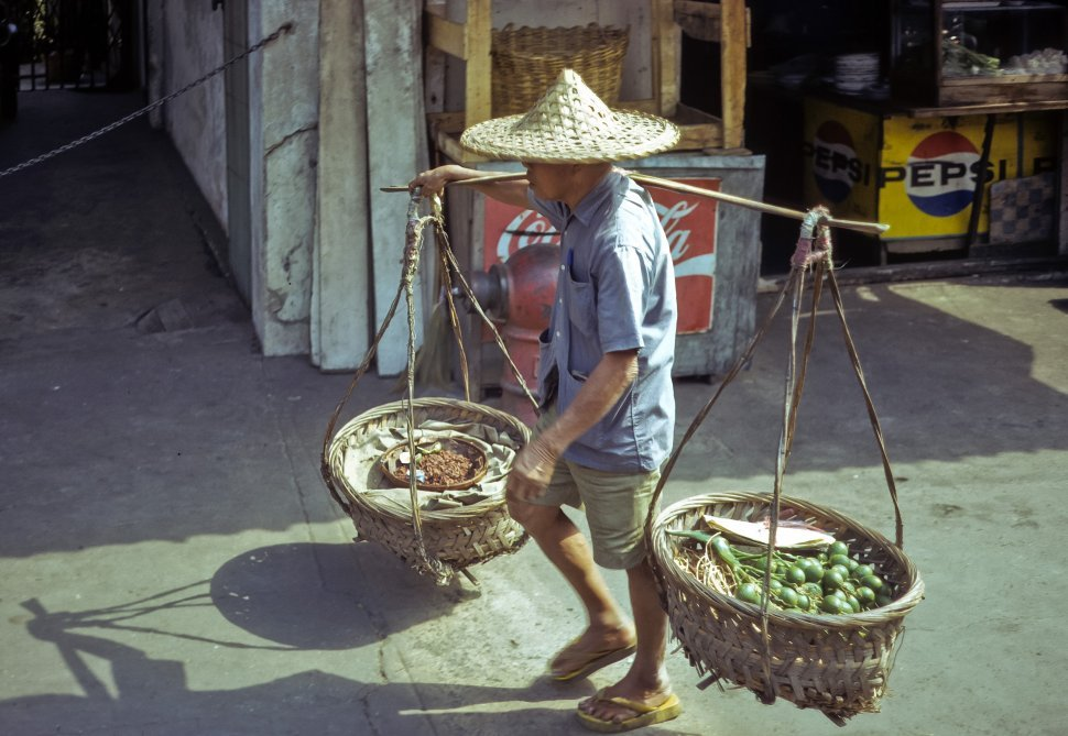 Free image of Local man carrying food in baskets balanced on his shoulders, circa 1974, Hong Kong, China