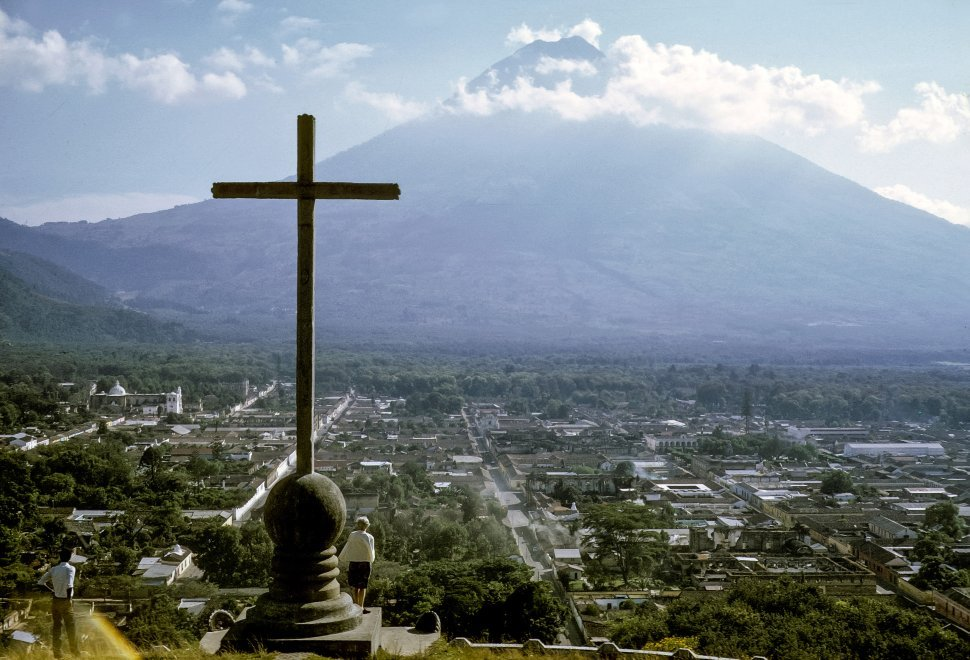 Free image of Man and woman looking down from cross at aerial view of city and volcano, circa 1969, Antigua