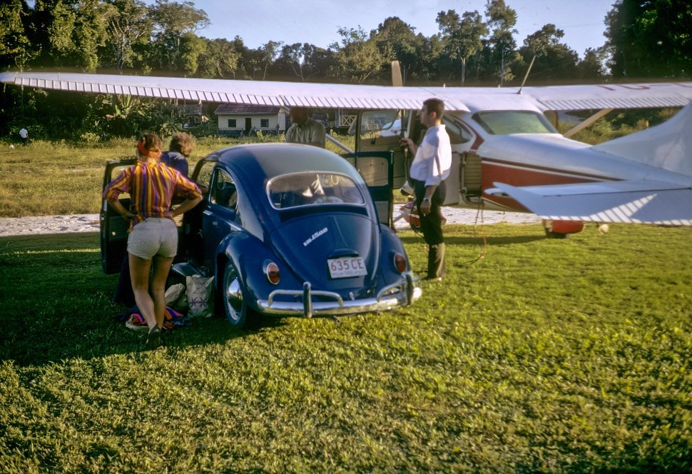 Free image of Men standing next to a small plane and Volkswagen, Chichicastenango, Guatemala