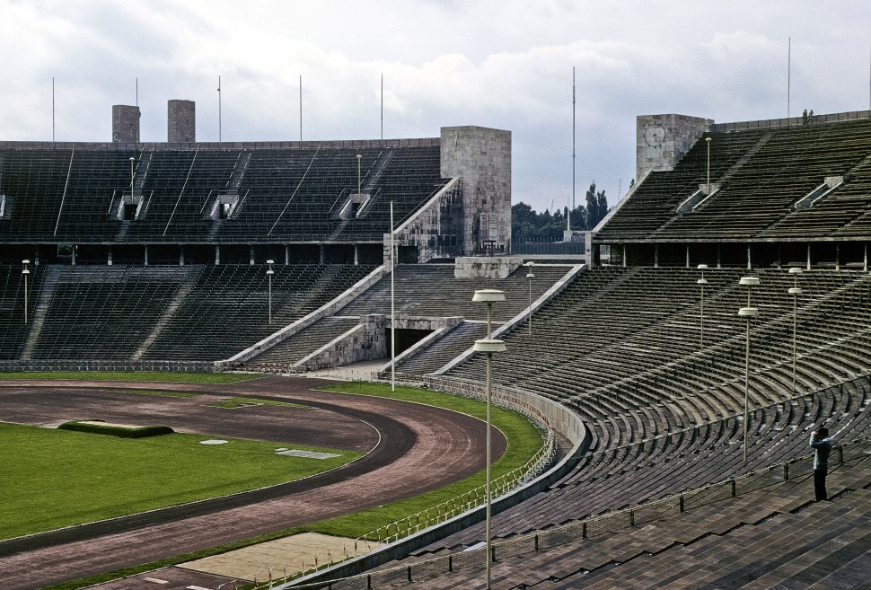 Free image of Man standing inside an empty Olympic stadium, circa 1968, East Berlin Germany