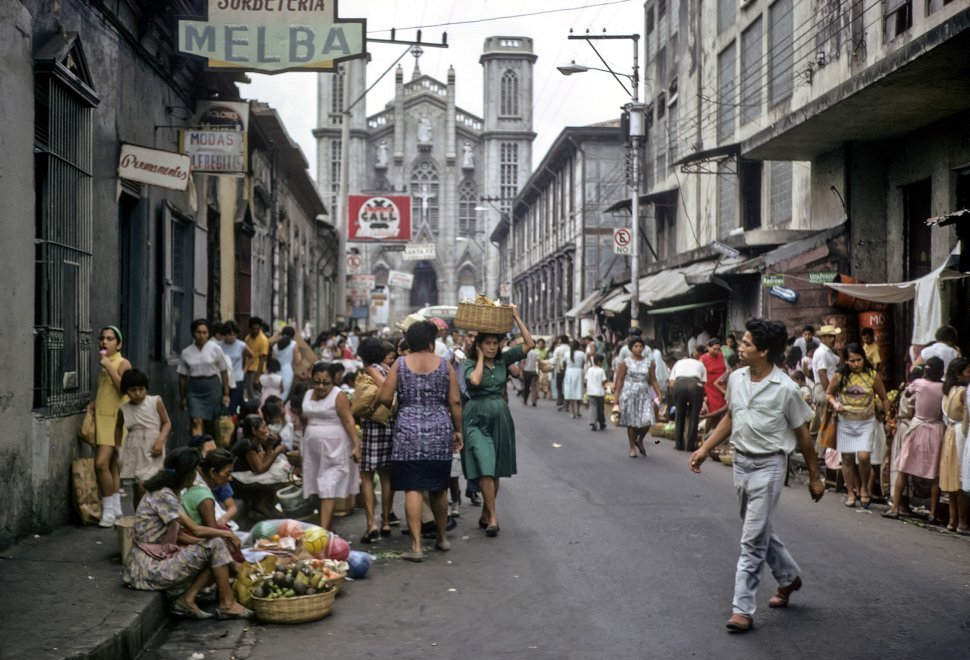 Free image of Woman balancing a basket on her head while walking through a busy marketplace, San Salvador