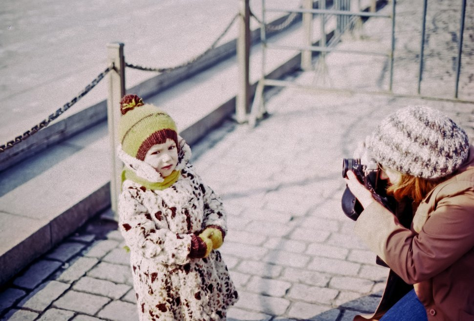 Free image of Child posing for a photograph taken by her mother, Red Square, Moscow, Russia