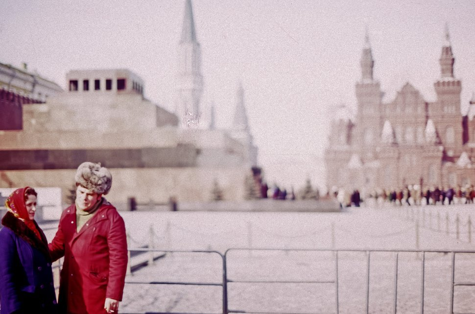 Free image of Couple standing in front of large building conversing in the cold, Red Square, Moscow, Russia