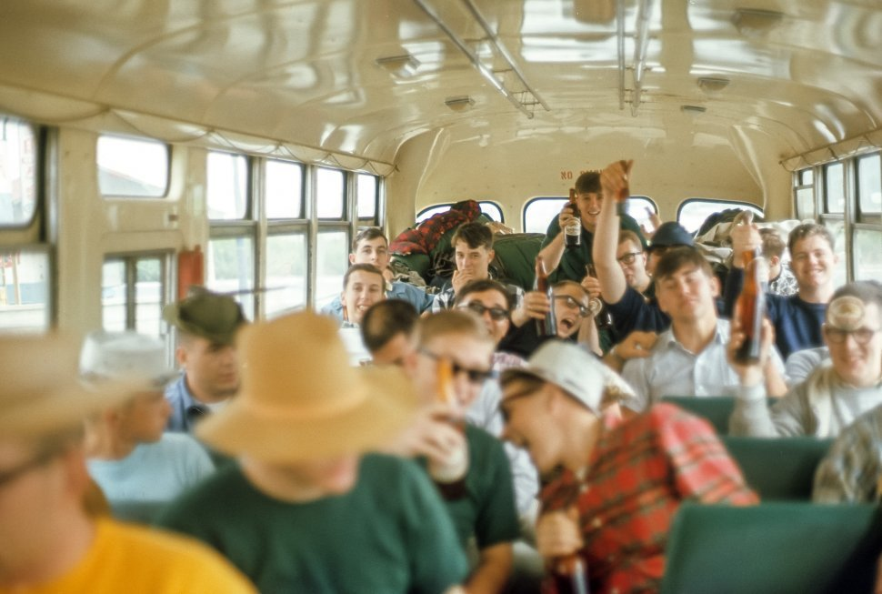Free image of Group of young men in the rear of a bus drinking beers.