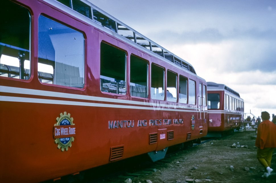 Free image of Two red trolley cars sitting on the tracks while tourists mill about. Manitou and Pike s Peak Railway, Cog Wheel Route, Colorado, USA