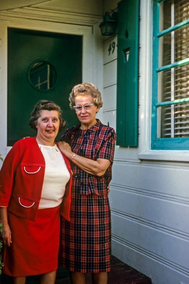 Free image of Two women smiling on the front step of a house, USA