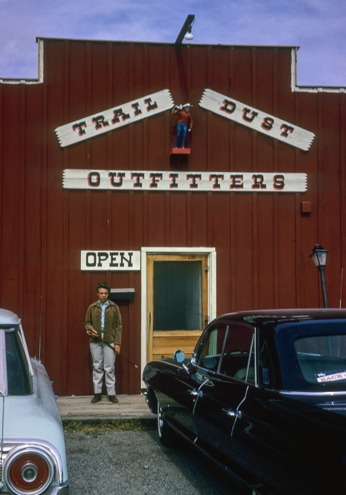 Free image of Man posing in front of a tourist stop and trading post, USA