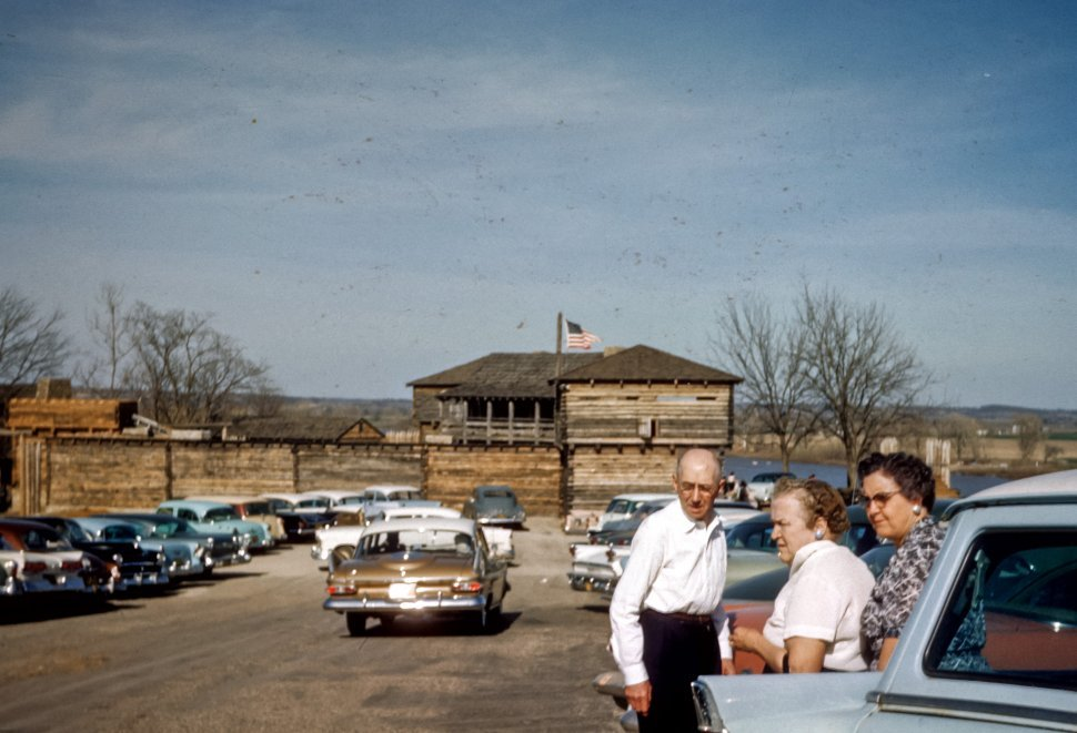 Free image of Three people looking at vintage cars in parking lot of a log fort, USA