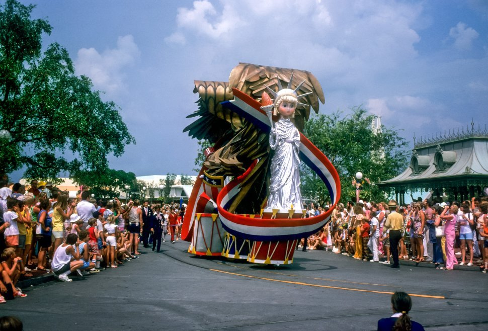 Free image of Crowd at a Disneyland parade with a Staue of Liberty float passing by, Anaheim, California, USA
