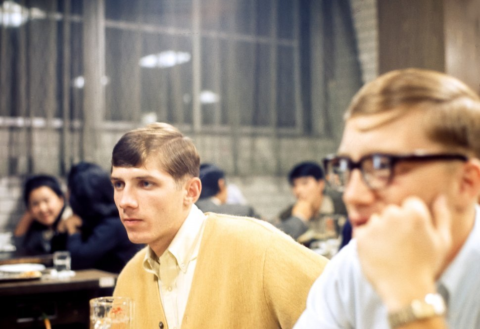 Free image of Two young men listening intently at a dinner gathering, Asia