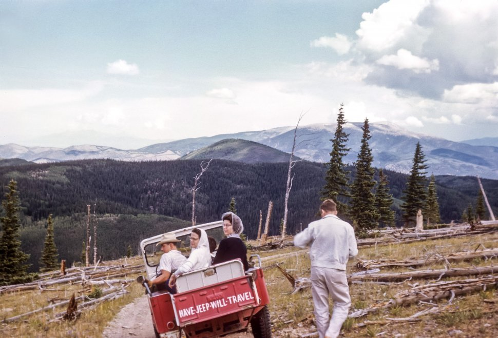 Free image of Tourists riding along a mountain road in a Jeep with a man standing nearby, USA