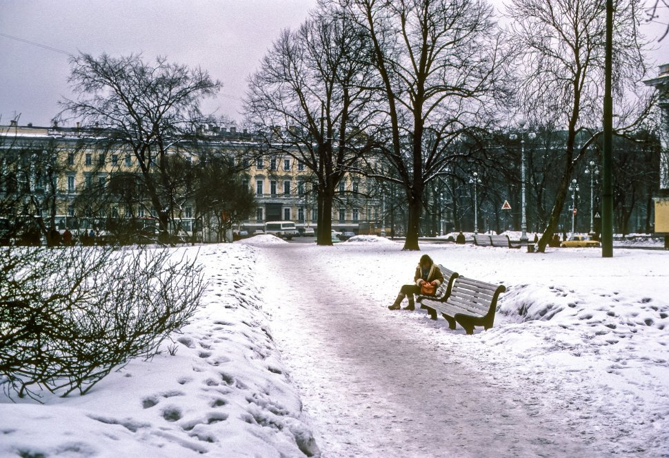 Free image of Woman sitting on a snowy park bench, Europe