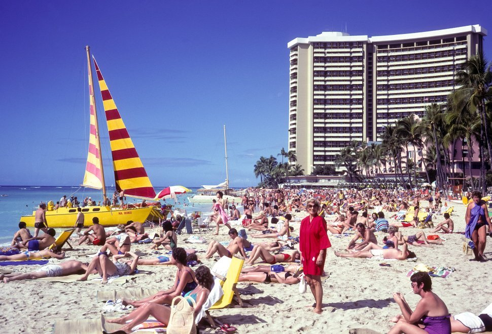 Free image of Woman posing in a huge crowd of tourists on a beach in front of a hotel, Hawaii, USA