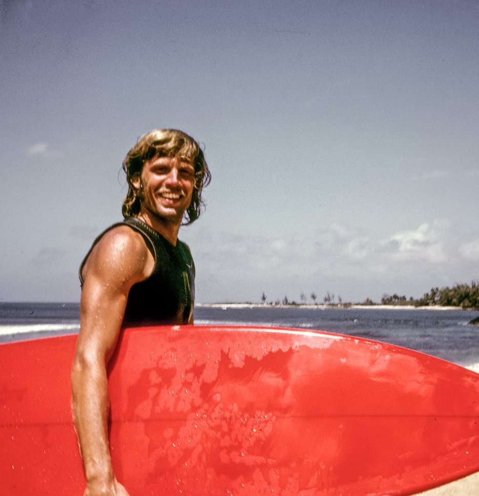 Free image of Young surfer smiling at the camera while carrying his surfboard on the beach.