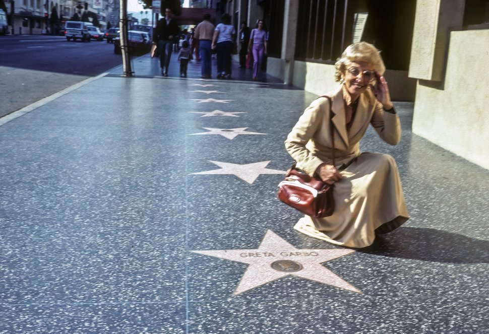 Free image of Woman posing next to the Gretta Garbo s star on the Hollywood Walk of Fame, Hollywood, California, USA