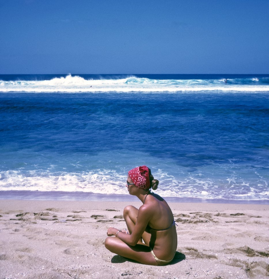 Free image of Woman sitting on the white sand in the sun on the beach, Hawaii, USA