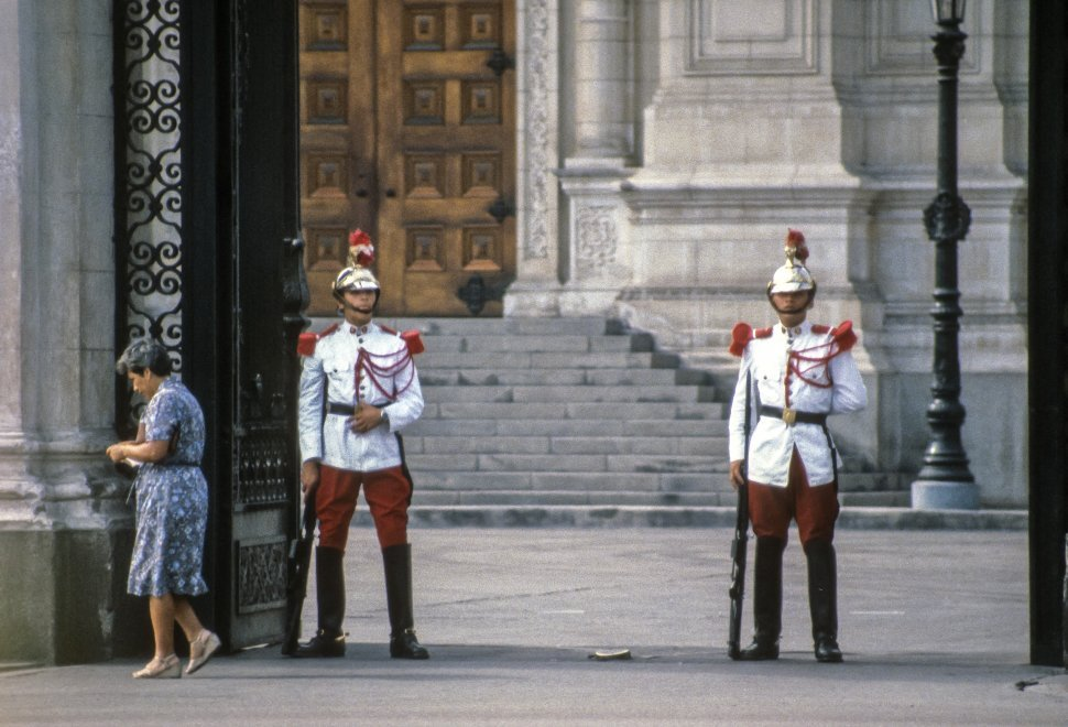 Free image of Woman walking past a palace and its uniformed guards