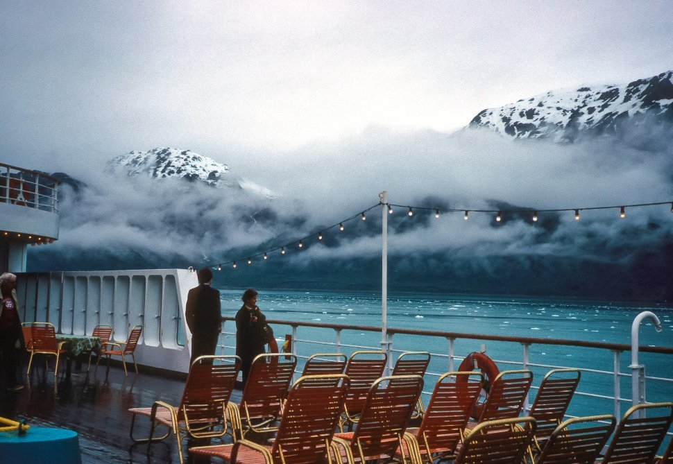 Free image of Two people at the side of a cruise ship, watching icebergs floating by, Alaska, USA