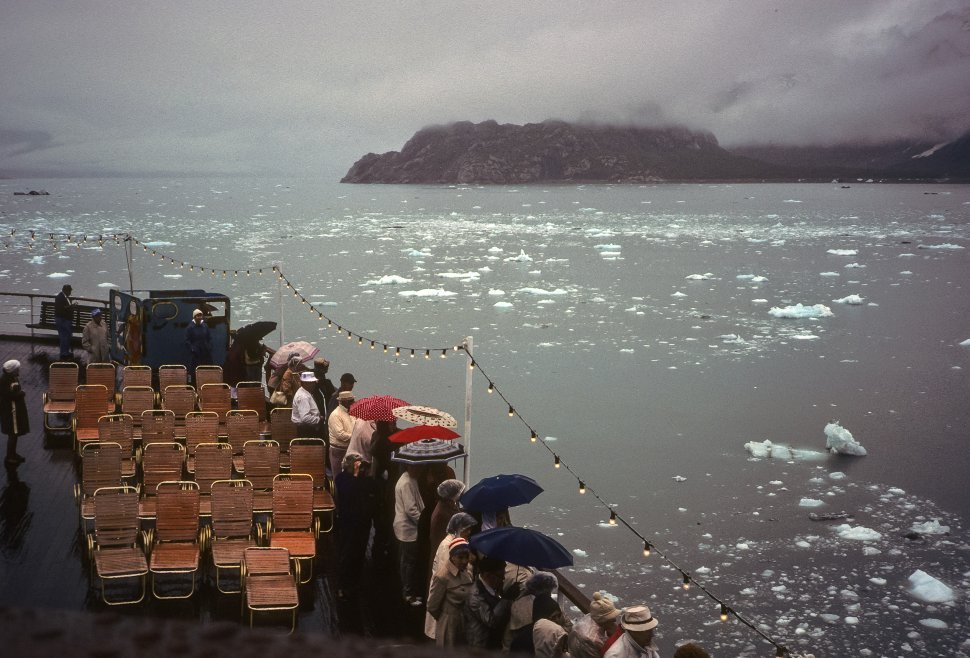 Free image of Large crowd of people at the side of a cruise ship, watching icebergs floating by, USA