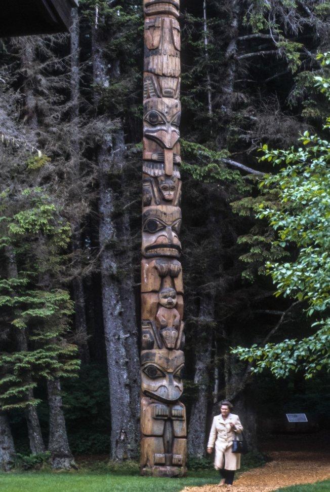 Free image of Woman walking below a tall totem pole, USA