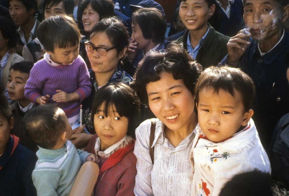 Free image of Mother holding her child in the midst of a large crowd, China